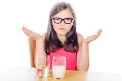 Lite har flickan ett val mellan ett exponeringsglas av vatten och ett exponeringsglas Royaltyfri Bild