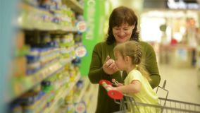 Lite hjälper sondottern hennes farmor med shopping De har så mycket gyckel tillsammans stock video