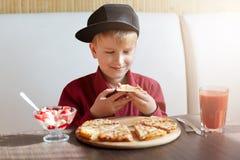Lite iklädd röd skjorta för pojke och modernt lock som placerar i restaurang på tabellen som smakar delisious pizza och glass som royaltyfria bilder