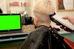 Lite klipper pojken en frisör i salongen Ungen håller ögonen på en tecknad film Grön skärm på en bärbar dator för häfte arkivfoto