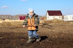 Lite krattar pojken som rymmer ett stort, i hans händer hjälper att arbeta på jordningen royaltyfria foton