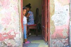 Lite kubansk flicka som kikar formen bak dörren royaltyfri fotografi