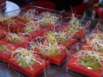 Lite kvadrerade Glass bunkar med alfalfa och gräsplan och tomat Sau royaltyfria foton