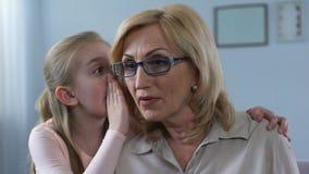 Lite länge förvånade den haired flickan som viskar hemlighet, grandmom, familjanslutning stock video