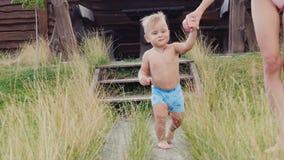 Lite lär pojken att gå, hans moder leder honom vid handen Ha en vila tillsammans på semesterorten arkivfilmer