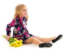 Lite ligger flickan på golvet med en bukett av tulpan royaltyfri bild