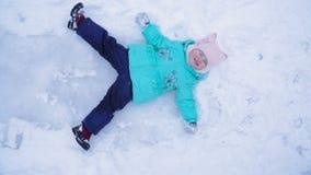 Lite ligger vinkar ser flickan på isen, henne ben och upp arkivfilmer