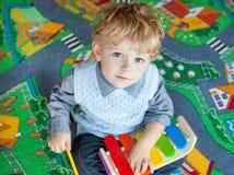 Lite litet barnpojke som leker med trämusiktoyen Arkivbilder