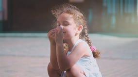 Lite lockig-haired flicka som skrattar på det lilla havsskalet och spelar med det En charmig flickaresande med henne lager videofilmer