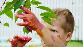 Lite målar barnet, en fyraåringpojke som spelar och att måla med fingret och att dekorera sidor på träden i trädgården stock video