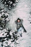 Lite omger flickan i vinterkläder som ligger på en snöig äng arkivfoto