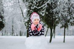 Lite parkerar flickasammanträde på insnöad vinter Royaltyfria Foton
