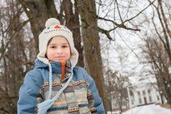 Lite parkerar pojken i vinter royaltyfri bild