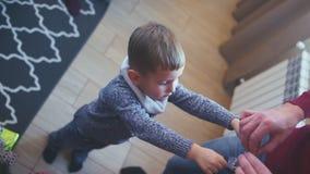 Lite pojke 5-7 gamla år dekorera en julgran stock video