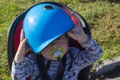 Lite pojke i en cykelstoldon& x27; t önskar att vara på hjälmen Royaltyfri Fotografi