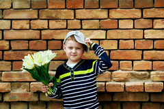 Lite pojke med en bukett av gula tulpan Royaltyfria Bilder