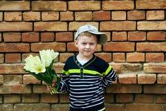 Lite pojke med en bukett av gula tulpan Royaltyfri Fotografi