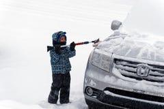 Lite pojke som borstar snö från en bil arkivfoto
