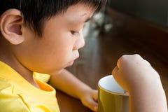 Lite pojke som hemma sitter p? tr?tabellen vid f?nstret f?r att dricka en kopp av varm choklad han rymmer koppen i hans v?nstra h arkivbilder