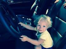 Lite pojke som låtsar för att köra en bil Fotografering för Bildbyråer