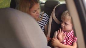 Lite pojke som sitter i ett bilsäte som sitter bredvid hans moder lager videofilmer