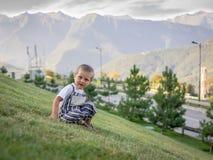 Lite pojke som sitter på en grön lutning royaltyfri bild
