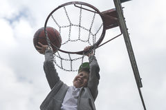 Lite pojkebanhoppning och danandemål som spelar streetball, basket Kastar en basketboll i cirkeln Begreppet av sporten Royaltyfri Fotografi