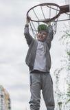 Lite pojkebanhoppning och danandemål som spelar streetball, basket Kastar en basketboll i cirkeln Begreppet av sporten Royaltyfria Bilder