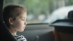 Lite rider flickan i busssammanträdet vid fönstret stock video