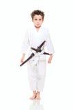 Lite rolig pojke i kimono med svärd royaltyfri foto