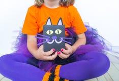 Lite rymmer flickan i en häxadräkt en svart katt arkivbild