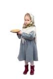 Lite rymmer flickan i traditionell slavicsjalett en platta av pannkakor Arkivbilder