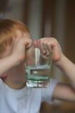 Lite rymmer pojken glas av vatten royaltyfria bilder