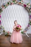 Lite rymmer prinsessan i en härlig rosa färgklänning en bukett av pioner, magnolian, bär och grönska mot en vit vägg a arkivfoto