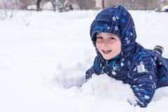 Lite ser barnet ut ur snön eller styckena av is Ett barn p royaltyfria bilder