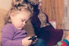 Lite ser flickan utan förälder`-uppmärksamhet smartphonen arkivfoton