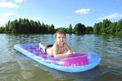 Lite simmar pojken i floden. royaltyfri bild
