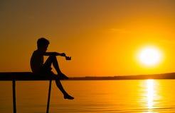 Lite sitter barnet på en bro med ben ner och lekar med pappersskeppet i hans hand på solnedgången på floden royaltyfri fotografi