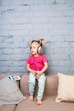Lite sitter den roliga flickan av två år på soffan som lyssnar till musik på pålagd hörlurar hennes huvud Rymmer en smartphone royaltyfria bilder
