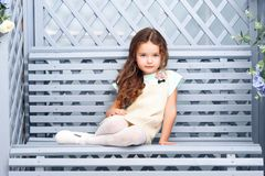 Lite sitter flickan av sju med kastanjebrunt hår på en träbänk i enblått färg och att le med ljus kläder och krullning _ Arkivfoton