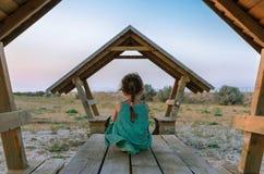 Lite sitter flickan i en bortvänd grön klänning och bara royaltyfria bilder
