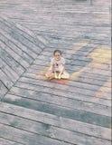 Lite sitter flickan i en lotusblomma poserar på ett trägolv fotografering för bildbyråer