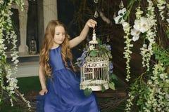 Lite sitter flickan i träna med felika vingar för gnistrandet som ser en magisk fågelbur för en fantasi eller Royaltyfri Foto