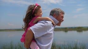 Lite sitter flickan med hennes farfar på hennes baksida, dem kör längs sjön 4K l?ngsam mo arkivfilmer