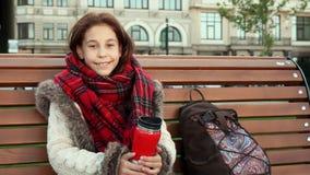 Lite sitter flickan på en bänk i en storstad royaltyfria bilder