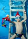 Lite sitter pojken i ett lock Santa Claus med en gåva i hand undervattens- på trappan som är längst ner av pölen Arkivbild