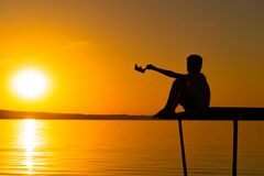 Lite sitter rymmer pojken på en bro och pappersskeppet i hans hand på solnedgången på floden En unge spelar med egen origami arkivbilder