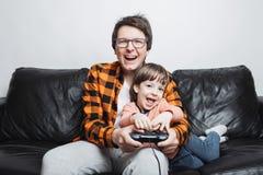 Lite sitter spelar den stiliga pojken och hans farsa på soffan hemma och videospel med styrspaken Farsan och sonen har gyckel arkivfoto