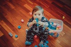 Lite sitter spelar pojken på golvet och med formgivaren fotografering för bildbyråer