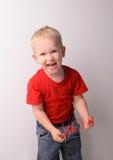 Lite skratta den blonda pojken i röd skjorta arkivfoto